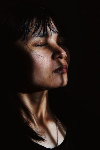 Close-up of woman sweating against black background