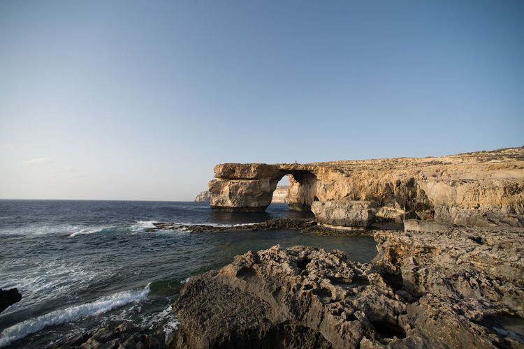 Scenic view of azure window on sea against clear sky