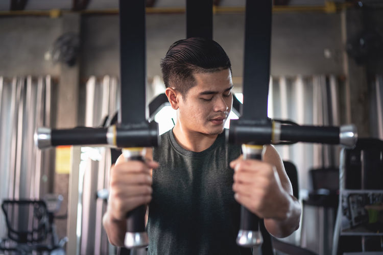 Young man exercising at gym