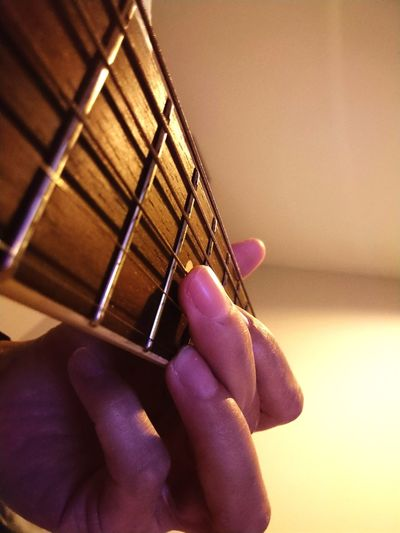 Close-up of hand playing guitar