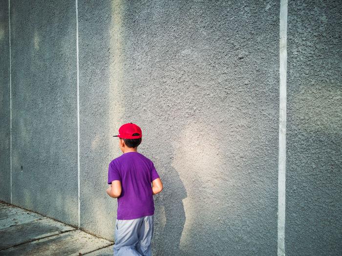 Boy running on footpath by concrete wall