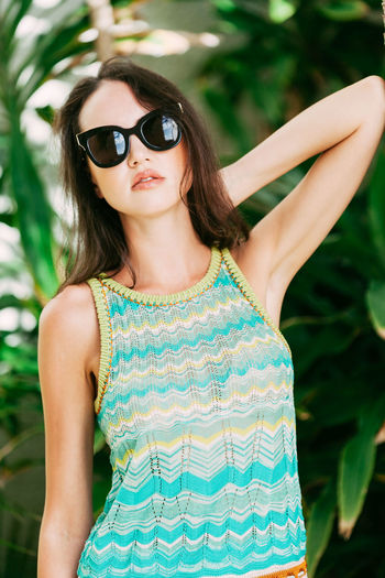 Beautiful woman wearing sunglasses standing against plants
