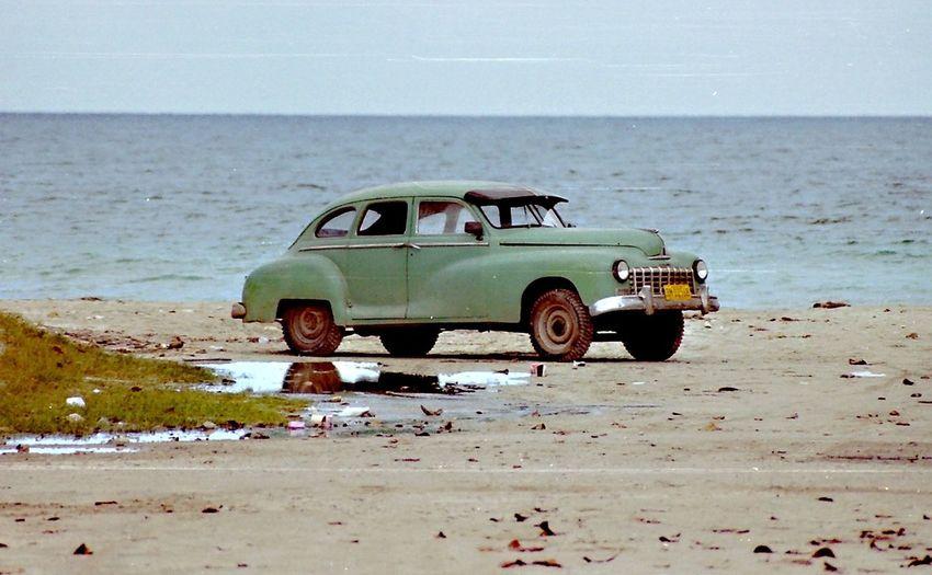 Toy car on beach against clear sky