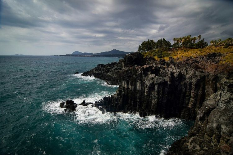sea nature rock - object adventure outdoors beach wave beauty in nature water mountain day scenics landscape sky ocean Korea Jeju island Dramatic sky dramatic cliff South Korea no people Jusangjeolli Jusangjeollicliff