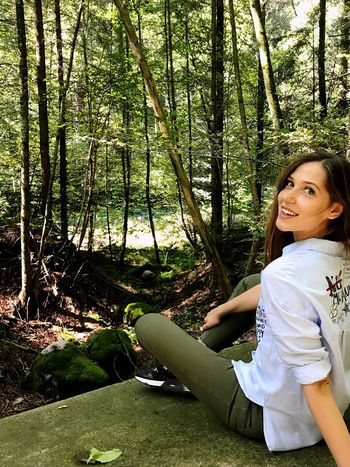 Forest Smiling Nature Green Color Sitting Outdoors Tree Trunk Day Beauty In Nature Switzerland Landscape Tree One Person Young Adult Growth Cheerful Portrait Young Women Women People Beautiful Woman One Young Woman Only