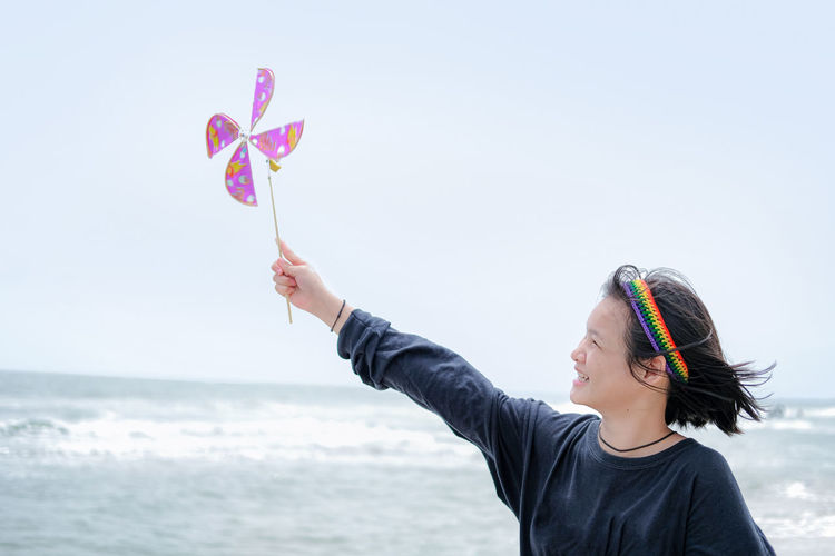 Portrait of woman holding umbrella on beach against sky