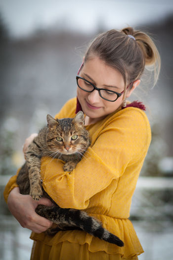 Woman holding cat while standing outdoors