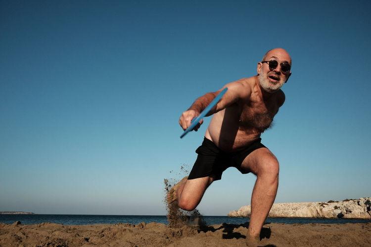 Man wearing sunglasses against clear blue sky playing beach tennis