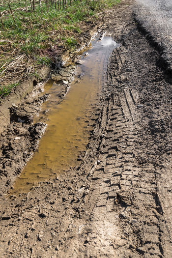 Outdoor Abstract Automobile Background Brown Car Direction Dirt Dry Field Grass Green Ground Land Landscape LINE Mark Mud Muddy Natural Nature Outdoors Path Pattern Puddle Rain Road Soil Surface Terrain Texture Tire Trace Track Tractor Transportation Travel Tree Truck Tyre Vehicle Vertical Water Wet Wheel White
