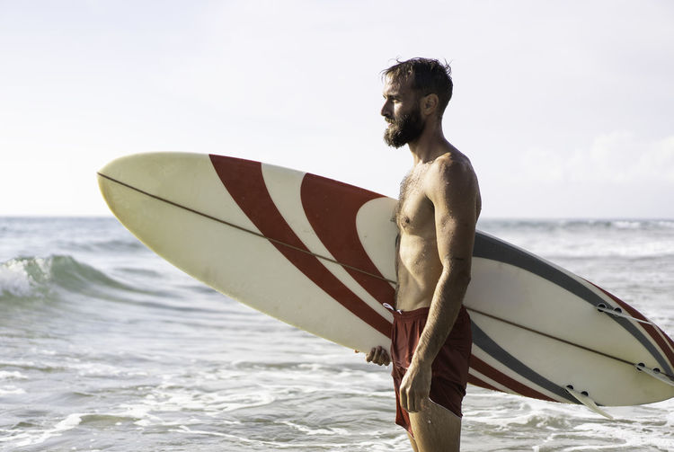 Young man with surfboard at beach against sky