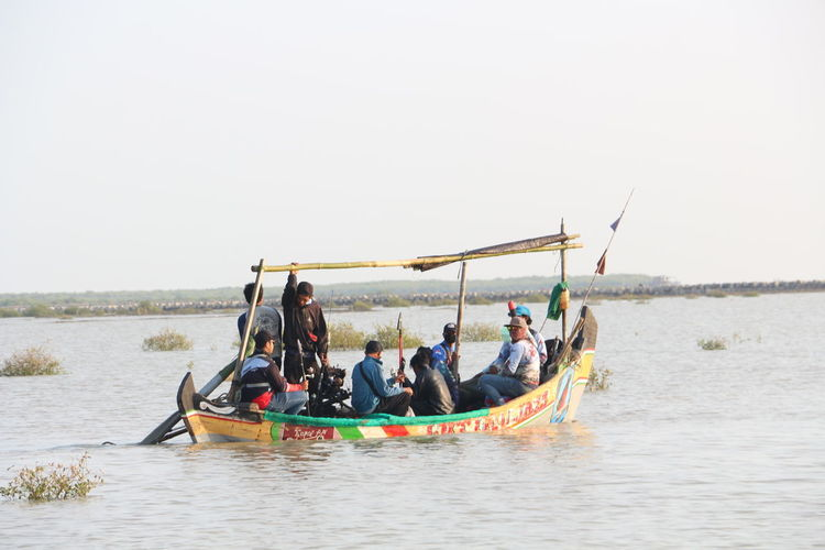 People in boat on sea against clear sky