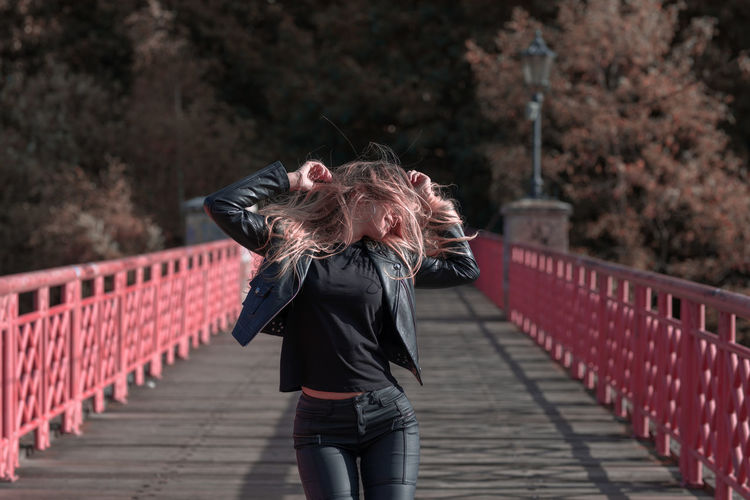 Young woman with blond hair standing on footbridge