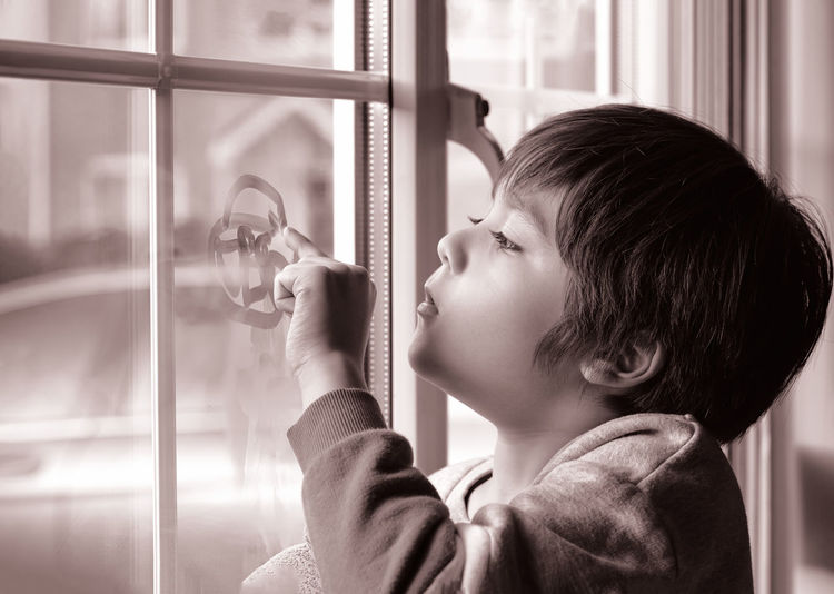 Close up of boy touching window at home