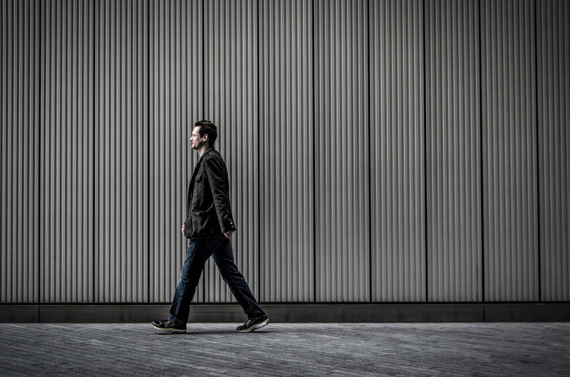 Side view of man walking on sidewalk by wall