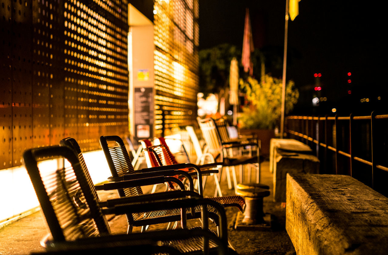 seat, architecture, built structure, chair, illuminated, night, absence, empty, building exterior, no people, table, focus on foreground, bench, city, nature, outdoors, building, business, selective focus, water