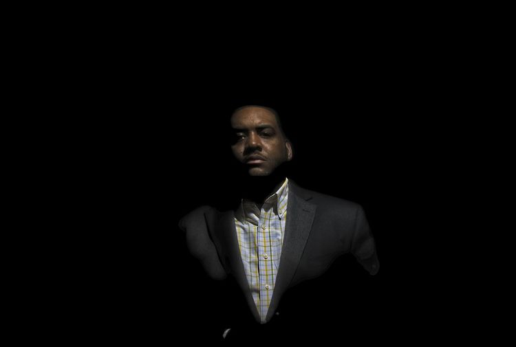Portrait of young man standing against black background