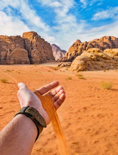 Man Holding Sand Against Sky