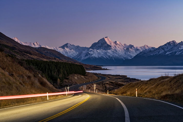 Light trails on road by mountains against clear sky