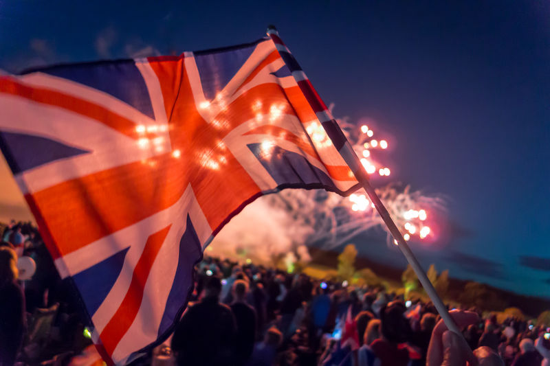 Close-up of british flag against crowd during firework display at night