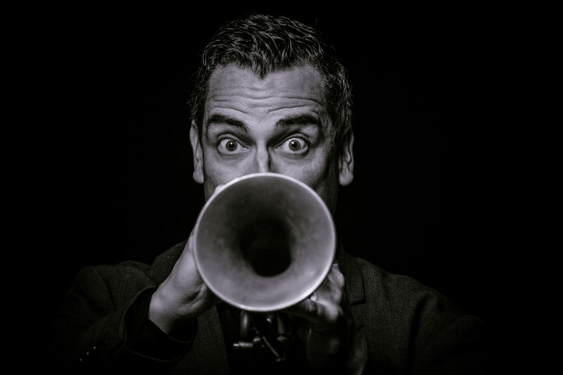 Close-Up Portrait Of Man Playing Trumpet Against Black Background