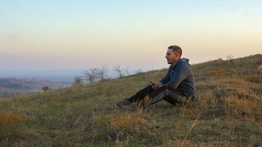Man sitting on mountain during sunset