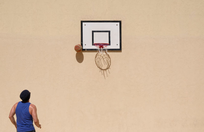 Man Playing Basketball Against Wall