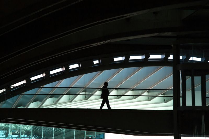 Low Angle View Of Silhouette Man Walking On Elevated Walkway At Railroad Station