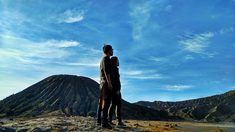 Couple Standing On Field By Mt Bromo Against Sky