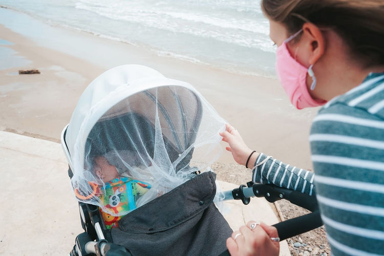 Mother wearing mask with baby on beach