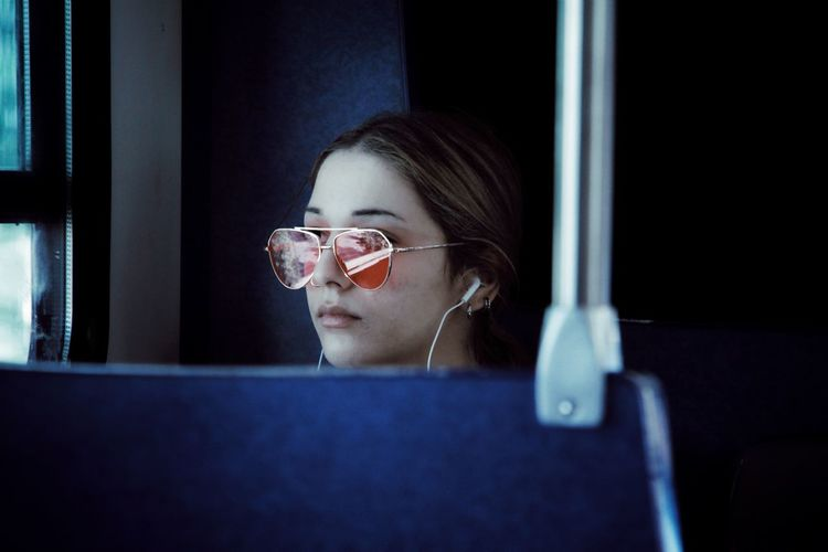 Young woman listening music while traveling in train