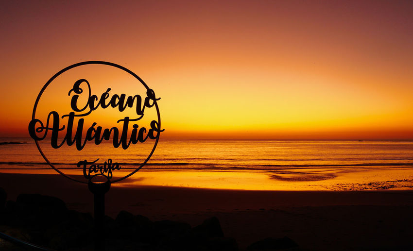 Silhouette text on beach against sky during sunset