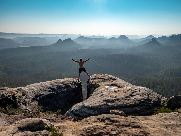 Shirtless male silhouette with raised arms on mountain top. sport life concept outdoor activities
