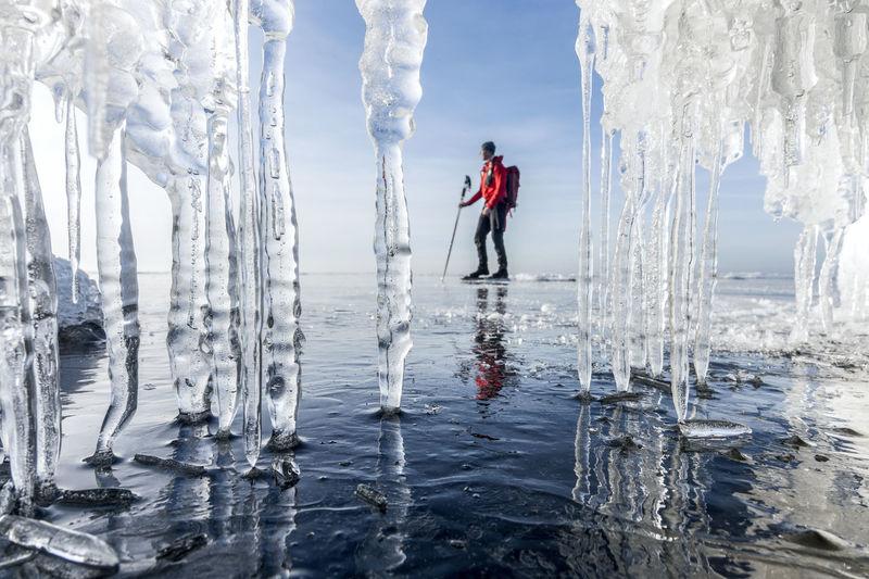 Full length of man standing in frozen lake