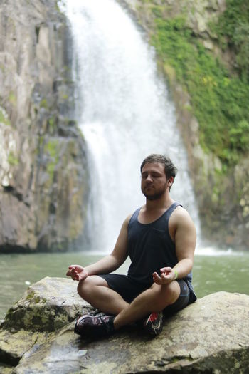 Young man sitting in lotus position on rock against waterfall