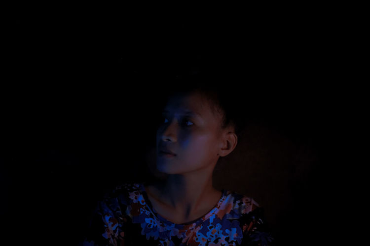 Portrait of girl looking away against black background