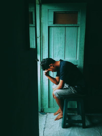 Side view of depressed man sitting at home