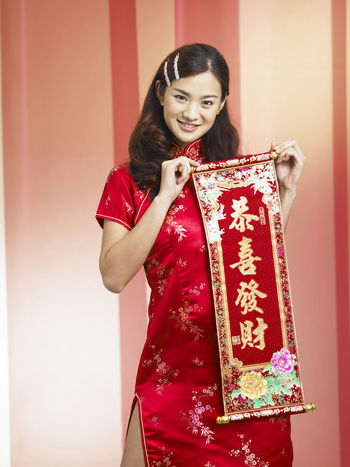 young chinese woman greeting during chinese new year Greeting Gong Xi Fa Cai Happiness Standing Woman Beautiful Woman Celebration Cheerful Cheongsam Chinese Characters Chinese Ethnicity Chinese New Year Color Background Cultures Curtain Happiness Portrait Qipao Red Scroll Smile Smiling Standing Traditional Clothing Young Adult