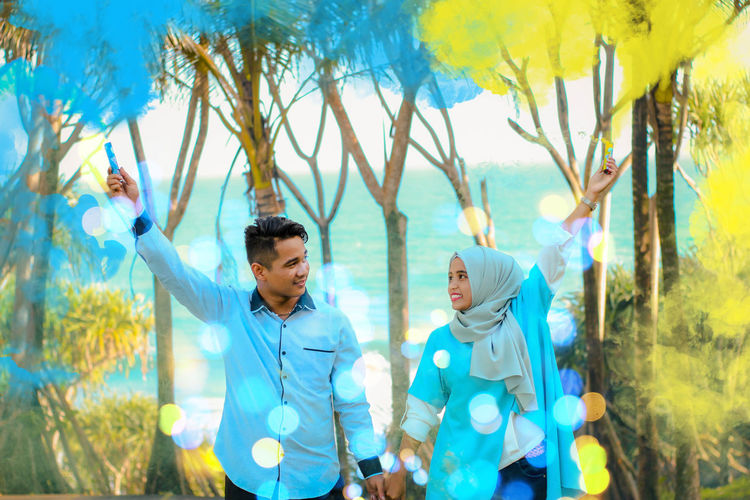 Couple holding smoke bombs while standing amidst trees