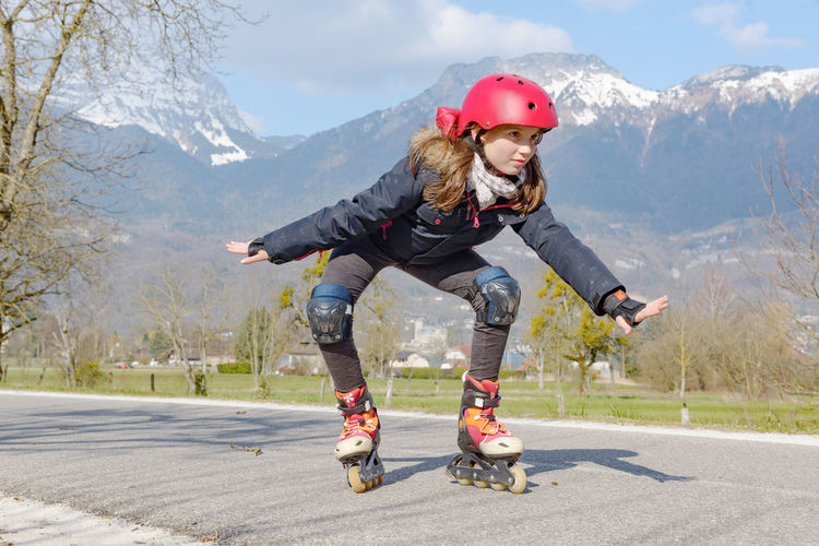 Child Childhood Cold Temperature Day Front View Full Length Helmet Leisure Activity Lifestyles Motion Mountain Mountain Range Nature One Person Outdoors Real People Road Sport Transportation Winter