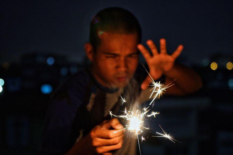 Man gesturing while holding sparkler at night