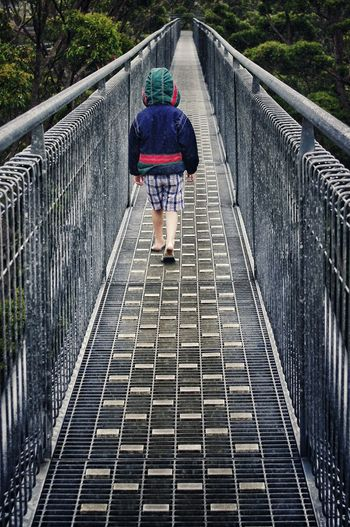 Boy Walking On Footbridge