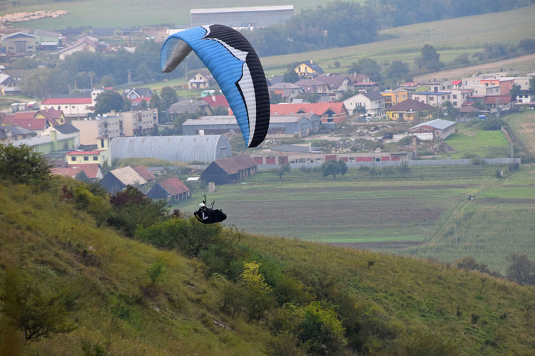 Paraglider flying over mountain in town
