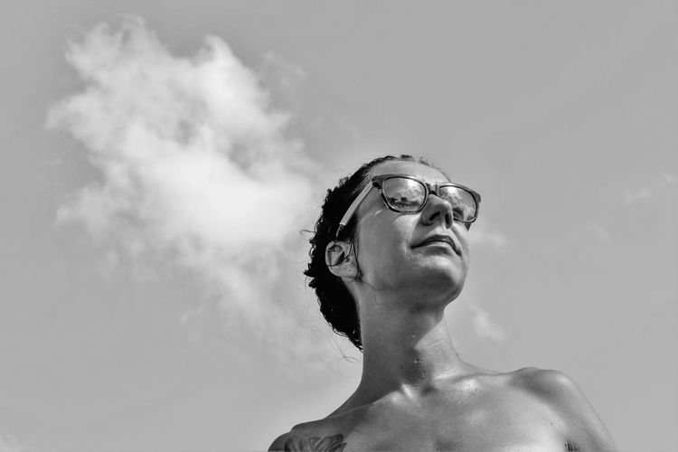 Low angle view of shirtless young woman wearing sunglasses while looking away against sky during sunny day