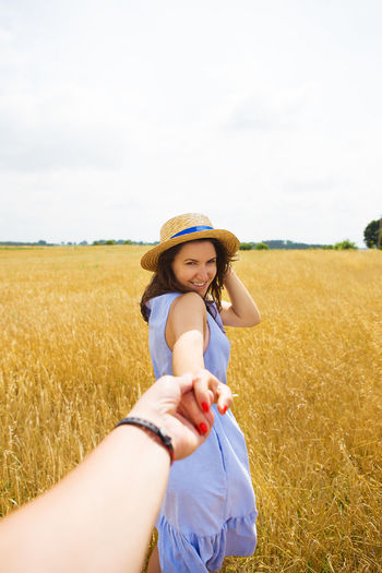 Happy woman wearing hat on field against sky