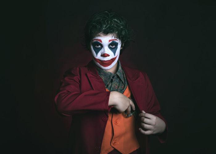 Portrait of boy wearing mask against black background