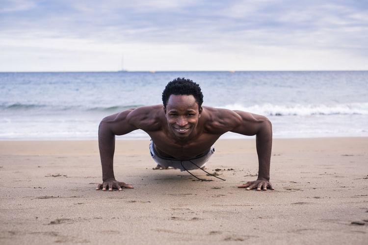 Portrait of man doing push-ups at beach