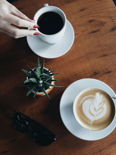 Cropped Image Of Woman Hand On Coffee By Potted Cactus On Table