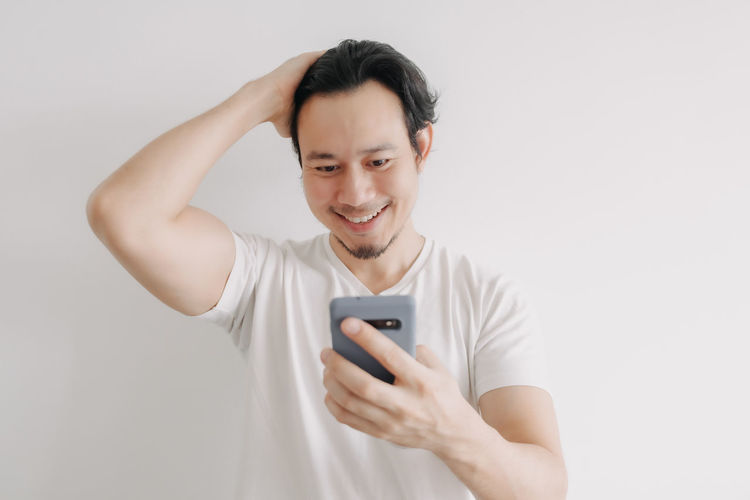 Smiling young man using smart phone against white background