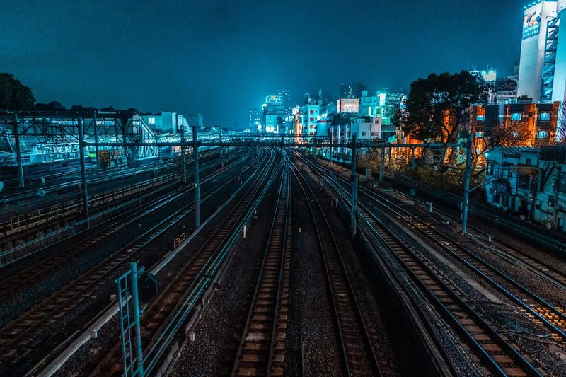 High angle view of railroad tracks amidst buildings at night