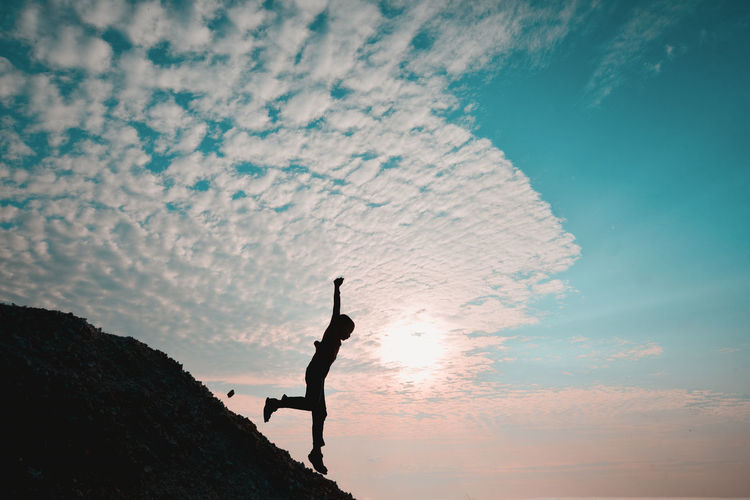 Silhouette boy with arms raised on rock against sky